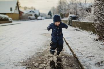 Baby boy walking on street in winter