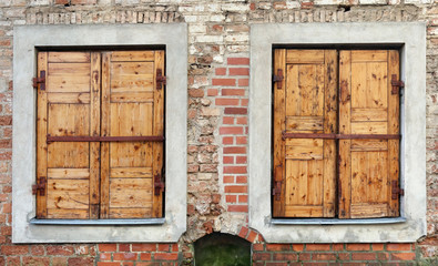 Two  windows  with closed locked  wooden blings in the aged brick wall of a ruined  house.