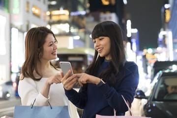 スマートフォンで場所を探している女性たち。