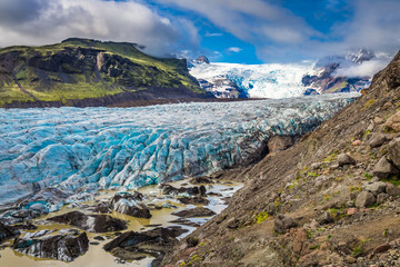 Blue glacier and green mountains in summer, Iceland
