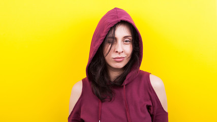 Cute woman with a hood on yellow background in studio