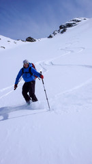 male skier and fresh tracks in untouched powder snow in the backcountry of the Swiss Alps