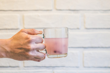 Pink cloudy drink with berries in a glass in a hand on a white background