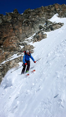 male extreme skier skiing down a very steep couloir in deep winter in the Swiss Alps near Klosters