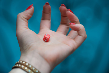 Red dice in woman's hand at the blue background