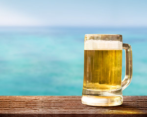 Glass of Beer on Wooden Table in front of the Sea, Blurred Blue Ocean and Sky as background