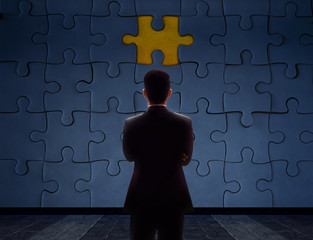 Work Problem Concept. Blurred Back side of a businessman Standing in front of blank Jigsaw Puzzle Wall to Finding a Lost Piece. Teamwork or Human Resource. Focus on background