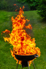 A big fire flashover a black grill outdoors when having a barbeque.