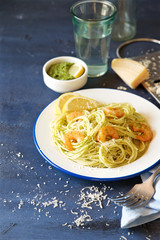 Spaghetti with green pesto, shrimps and cheese. Blue wooden background