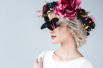 stylish girl posing in floral wreath with beautiful alive butterfly on face, isolated on grey