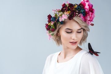 beautiful model posing in floral wreath with butterfly on shoulder, isolated on grey