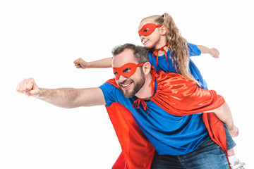 happy father and daughter in superhero costumes pretending to fly isolated on white