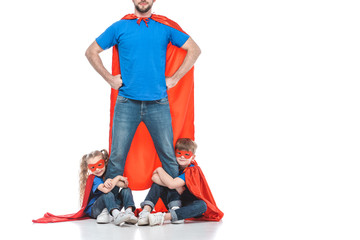 cropped shot of super dad standing with hands on waist while kids hugging his legs isolated on white