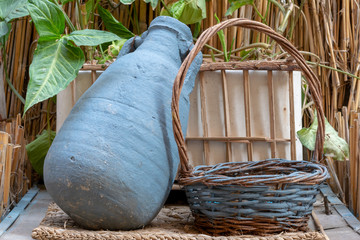 Blue pottery container and wicker basket on background of wooden cage and assembled reeds