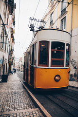 Classic tram with graffiti on old street, Lisbon, Portugal