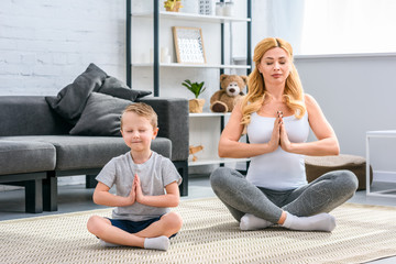 Young mother and son sitting with closed eyes and practicing yoga in lotus position