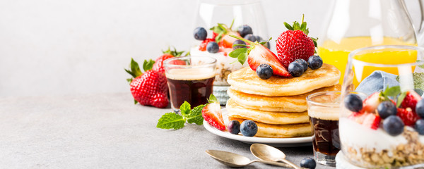 Breakfast composition with fresh pancakes and berries on light gray concrete background. Healthy food concept with copy space. Banner.