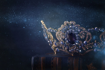 low key image of beautiful queen/king crown over wooden table. vintage filtered. fantasy medieval period.