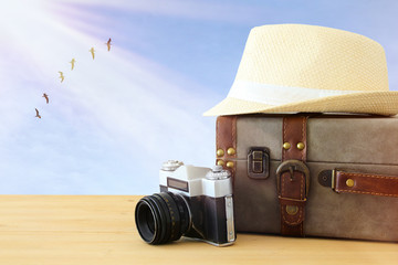 traveler vintage luggage, camera and fedora hat over wooden table infront of blue sky and birds. holiday and vacation concept.
