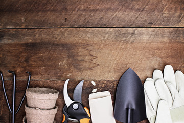 Background of various gardening tools, gloves and vegetable seeds shot from above over a rustic wood table in flat lay style.