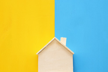Top view Image of colorful house model over double colorful background. Real estate concept.
