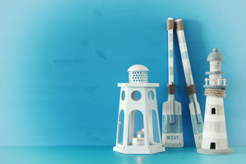 nautical concept with white decorative lantern, lighthouse and wooden boat oars over blue background.