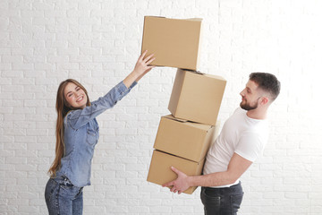 Relocation. Man giving cardboard boxes to the woman. Happy smiling woman looking at camera.