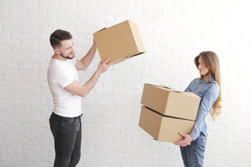 Relocation. Man giving cardboard boxes to the woman. Pretty, sad woman.