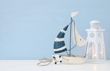 nautical concept image with white boat and lighthouse lantern over light blue background.