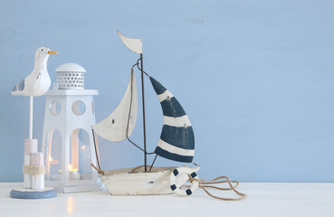 nautical concept image with white decorative seagull bird, boat and lighthouse lantern over light blue background.