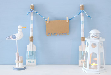 nautical concept with hanging empty note on a string next to lighthouse lantern and seagull over blue background.