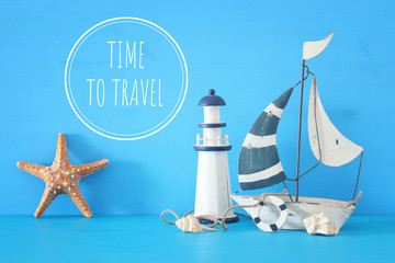 nautical concept with white decorative sail boat, lighthouse, starfish, seashells over blue wooden table and background.