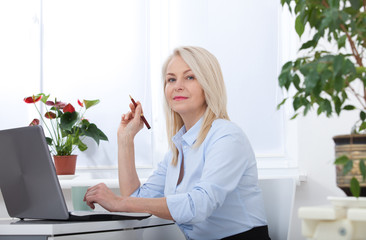 Pretty middle aged business woman working on computer in her office