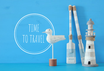 nautical concept with white decorative seagull bird, lighthouse and wooden boat oars over blue background.