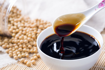 Pouring soy sauce into a white bowl