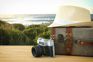 traveler vintage luggage, camera and fedora hat over wooden table infront of sunset landscape. holiday and vacation concept