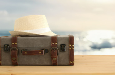 traveler vintage luggage and fedora hat over wooden table. holiday and vacation concept.