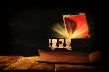 Image of mysterious treasure chest with light over old book on wooden table.