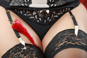 Woman wearing sexy panties having pepper on thigh