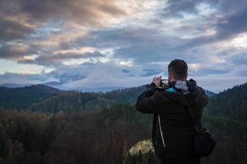 Mann fotografiert berg bei sonnenuntergang mit wolken