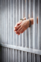 prisoner hands behind jail background.