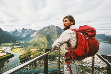 Tourist man sightseeing aerial mountains adventure Travel Lifestyle summer vacations in Norway traveler with backpack standing alone on Rampestreken viewpoint in Norway