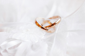 Pair of golden wedding rings on lace silk fabric with fabric flower. Wedding embroidery dress detail.