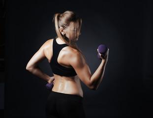 Sporty girl doing studio shot over black background