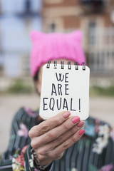 woman with a pink hat and the text we are equal.