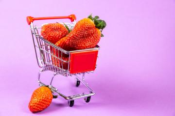 Shopping cart full of strawberries on purple background