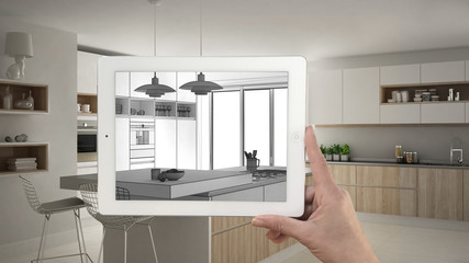 Hand holding tablet showing kitchen sketch or drawing. Real finished modern kitchen with island and stools in the background, architecture interior design presentation