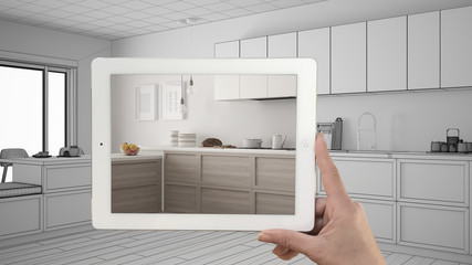 Hand holding tablet showing real finished minimalist white and wooden kitchen. Modern kitchen sketch or drawing in the background, architecture interior design presentation