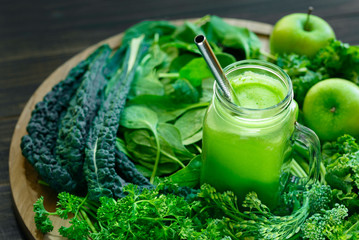 Cancer preventive leafy greens with a glass jar of fresh juice with a sliver drinking straw