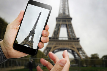traveler hand taking a photo of Eiffel Tower with smartphone during a weekend trip to Paris, France